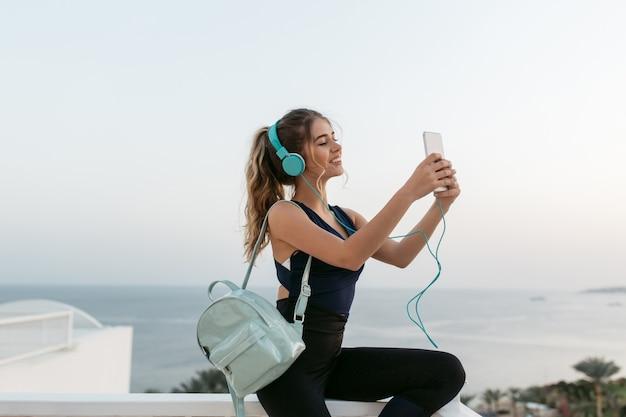 Incredibile giovane donna attraente giovane in abiti sportivi che fa selfie sul telefono in mattina di sole sul lungomare. resort, colori bianchi, allenamento, buon umore, ascolto di musica in cuffia