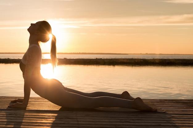 Incredibile giovane donna sportiva fa esercizi di yoga.