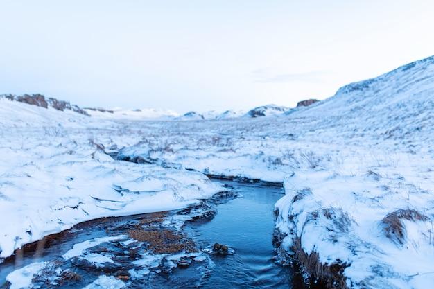 Incredibile paesaggio invernale dell'islanda. in inverno, una fonte di acqua calda scorre nelle montagne