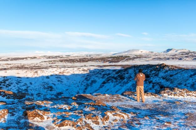 Incredibile paesaggio invernale vicino al lago kerid. il ragazzo cammina vicino al cratere del vulcano kerid in inverno.