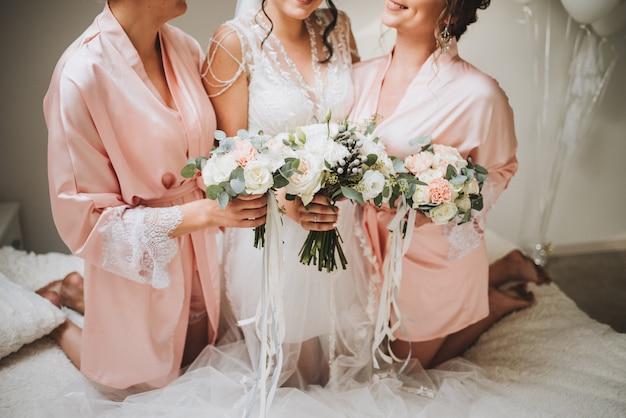 Incredibile sposa caucasica con le sue adorabili damigelle che tengono i mazzi di fiori la mattina del matrimonio