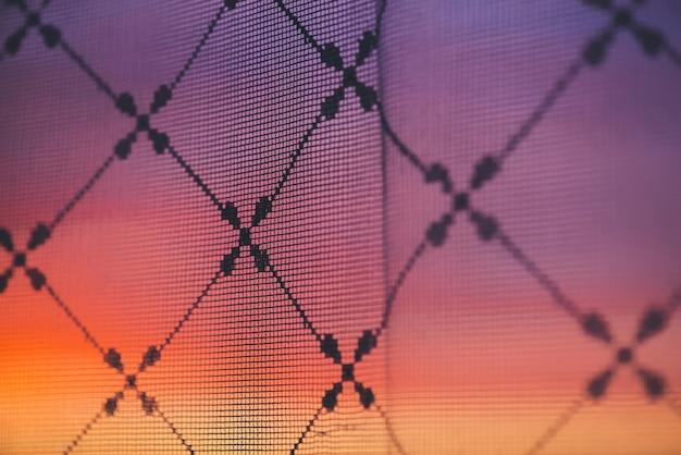 Incredibile tramonto romantico nella finestra dietro le sagome della trama di tulle. meraviglioso cielo rosa arancione viola alba dalla finestra attraverso la tenda a motivi geometrici.
