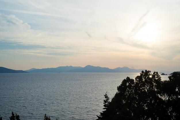 Incredibile tramonto sulla spiaggia con orizzonte infinito e incredibili onde spumeggianti. colline vulcaniche sullo sfondo