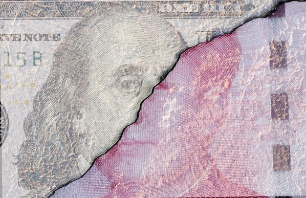 Incrinato di faccia a faccia della banconota da un dollaro americano e della banconota in cina