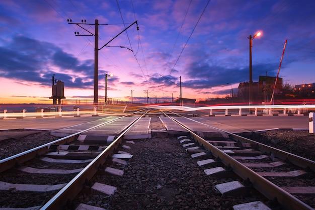 Incrocio di ferrovia con le luci dell'automobile nel moto alla notte