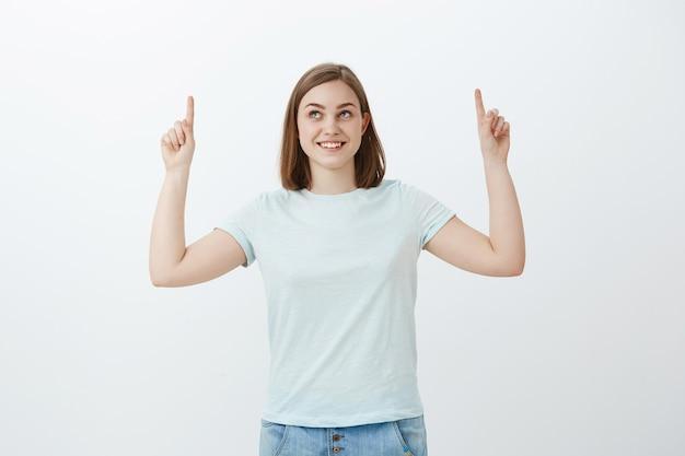 Incuriosita e gioiosa donna ottimista con un ampio sorriso curioso che punta e guarda in alto