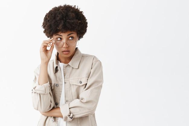 Incuriosito afroamericano di bell'aspetto, guardando da sotto gli occhiali, toccando il bordo degli occhiali e fissando a destra con espressione incerta sul muro grigio