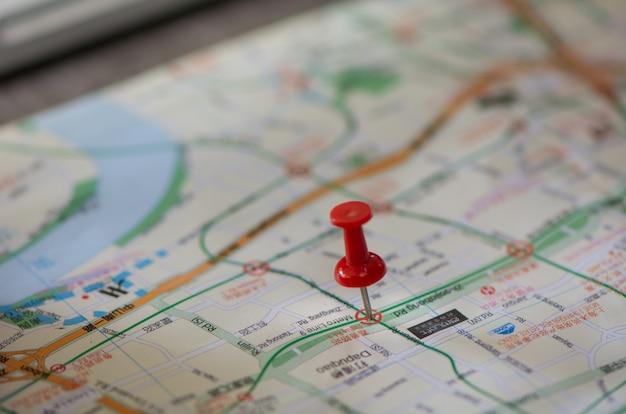 Indicando il programma rosso del perno per viaggiare sulla mappa, concetto di viaggio