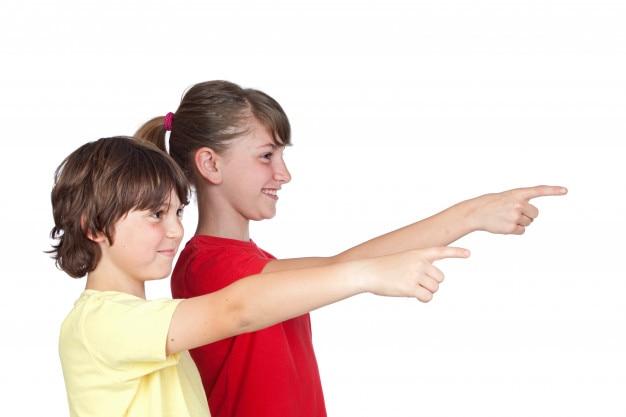 Indicare adorabile del dito della ragazza e del ragazzino del preteen isolato su fondo bianco