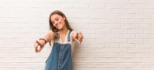 Indicare allegro e sorridente della giovane donna dei pantaloni a vita bassa la parte anteriore