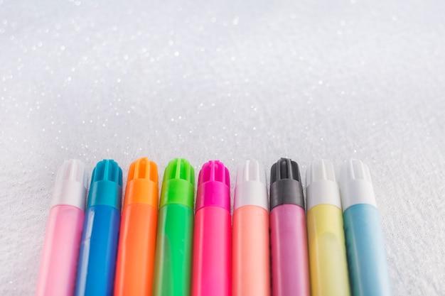 Indicatori colorati su sfondo bianco con glitter.