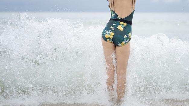 Indietro del basamento della donna sulla spiaggia. le onde le lavano i piedi.