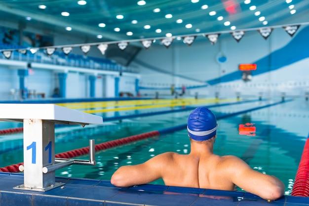 Indietro del nuotatore maschio che sta nello stagno