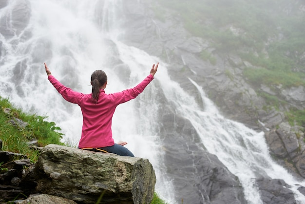 Indietro della bella giovane donna seduta su una grande roccia presso la grande cascata potente. bella ragazza che gode del tempo nebbioso della natura
