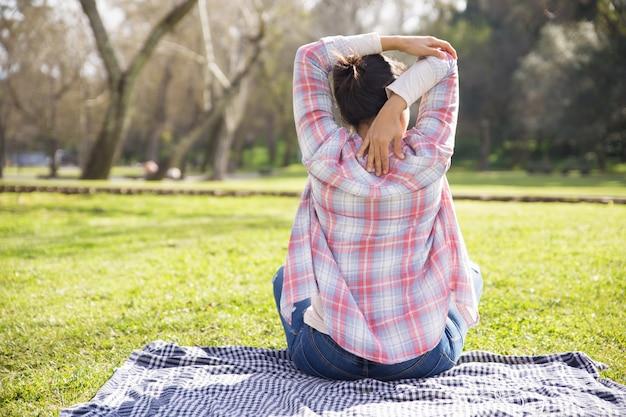 Indietro della ragazza in camicia a scacchi e jeans