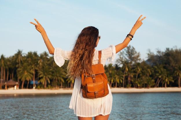 Indietro di bella donna in vestito bianco che cammina spensierata sulla spiaggia tropicale con zaino in pelle.