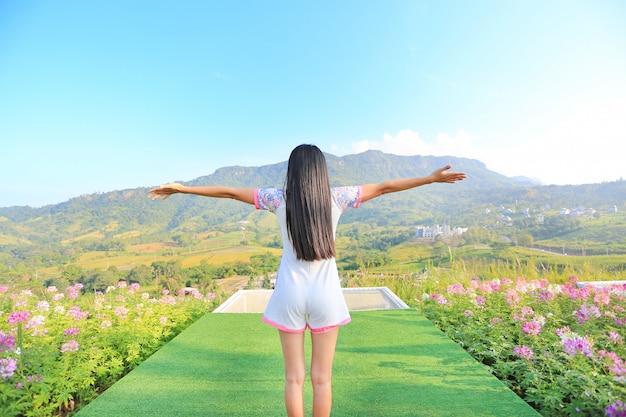 Indietro di giovane donna sentirsi libero con le braccia spalancate a bellissimi alberi e montagne in b