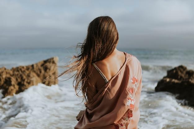Indietro di una donna seduta lungo la spiaggia
