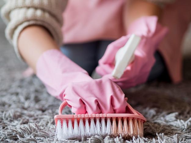 Individuo del primo piano che spazzola il tappeto