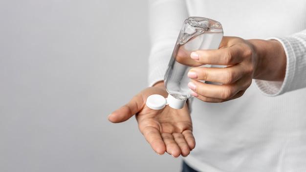 Individuo del primo piano facendo uso del gel di pulizia per le mani