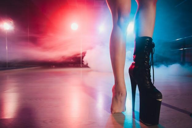Indossa uno stivale alto sulla piattaforma e sul tallone. ballerino di spogliarello che si muove sul palco nel night club di strip.