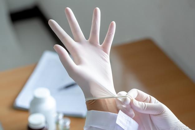 Indossare guanti di gomma per operazioni mediche.