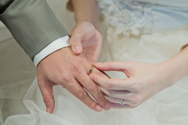 Indossare un anello, fede nuziale, coppia di innamorati