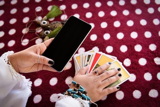 Indovino che legge le linee di fortuna sullo schermo smartphone moderni oroscopi applicazione di cartomanzia online.