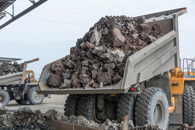 Industria mineraria: pesanti autocarri con cassone ribaltabile scaricano il granito in un enorme frantoio da roccia