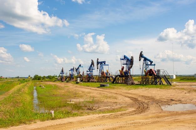 Industria petrolifera e del gas. martinetti della pompa dell'olio di lavoro in un giacimento di petrolio. nuvole bianche e cielo blu. produzione di petrolio e petrolio.