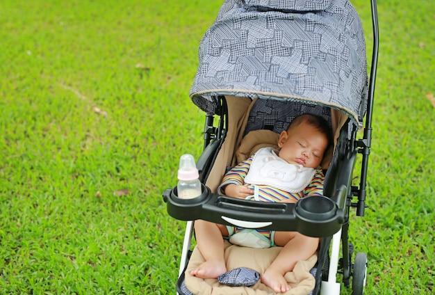 Infante asiatico che dorme in passeggiatore nel giardino verde