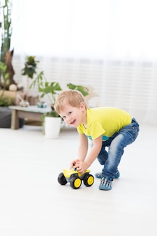 Infanzia felice - piccolo ragazzino allegro che gioca a casa con l'automobile del giocattolo