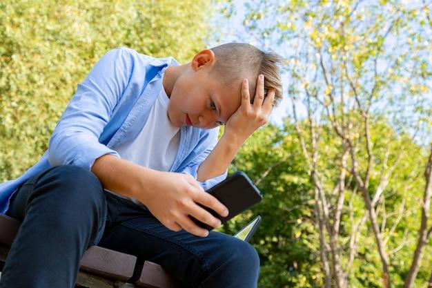 Infanzia, realtà aumentata, tecnologia e concetto della gente - il ragazzo con il fronte turbato esamina lo smartphone all'aperto all'estate
