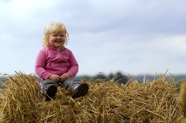 Infanzia sana in armonia con la natura - la ragazza felice si siede su un mucchio di fieno in un campo di grano