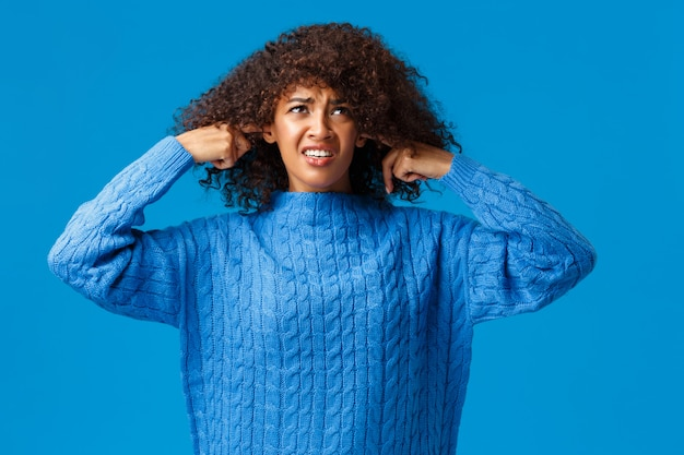 Infastidita e interrotta dispiaciuta studentessa di college afroamericana in maglione invernale, guardando in alto e facendo smorfie, chiudi le orecchie con le dita, non ascolta la musica terribile e rumorosa, i neigbours fanno festa