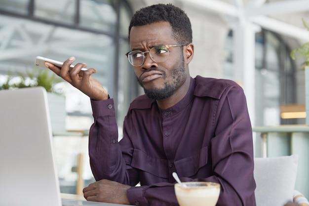 Infelice maschio dalla pelle scura in abbigliamento formale, tiene il telefono intelligente in attesa di una chiamata dal partner commerciale