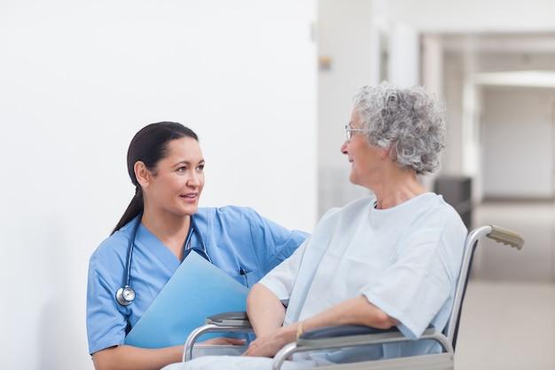 Infermiera accanto a un paziente in sedia a rotelle