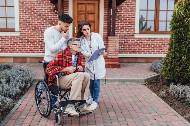 Infermiera alla ricerca di una cartella, vecchio in whelchair con suo figlio in attesa