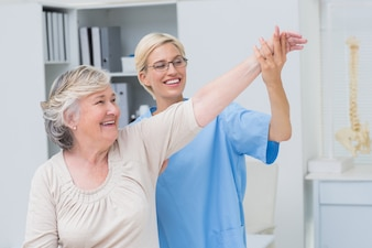 Infermiera che aiuta paziente senior nell'esercitazione