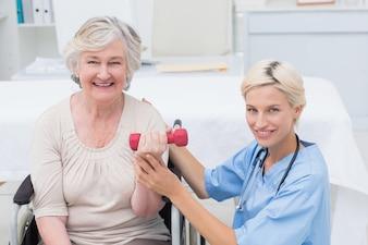 Infermiera che assiste il paziente femminile nel sollevamento del dumbbell