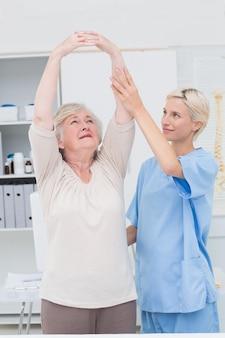Infermiera che assiste il paziente femminile nell'innalzamento delle braccia