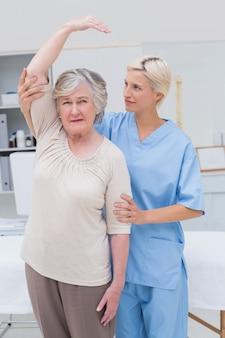 Infermiera che assiste il paziente senior nel sollevare il braccio
