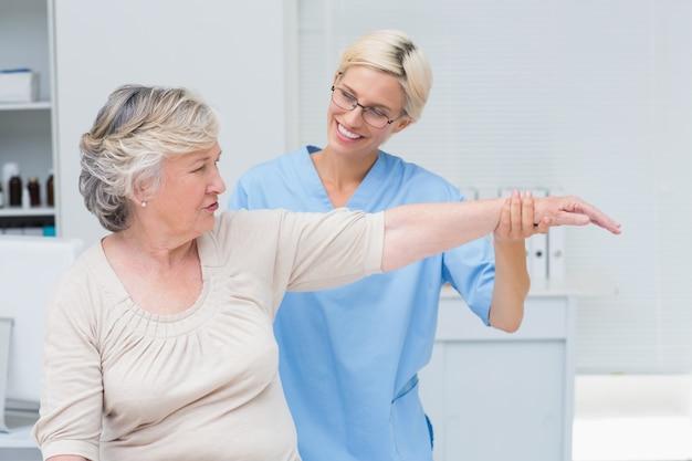 Infermiera che assiste il paziente senior nell'esercitarsi alla clinica