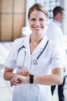 Infermiera che controlla il suo orologio intelligente all'ospedale