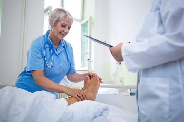 Infermiera che dà il trattamento del piede al paziente