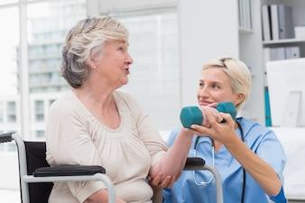 Infermiera che esamina paziente mentre la aiuta nel sollevamento del dumbbell