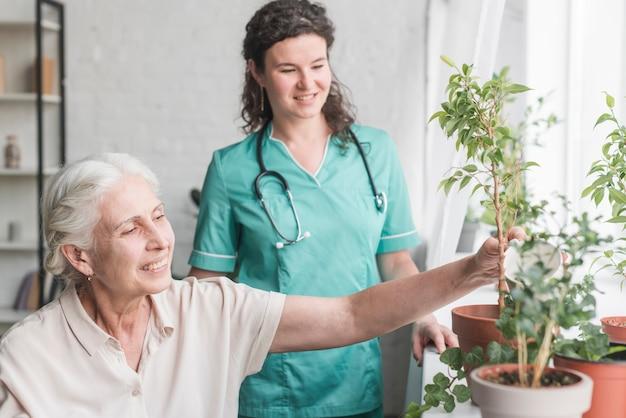 Infermiera che esamina paziente senior che innaffia la pianta