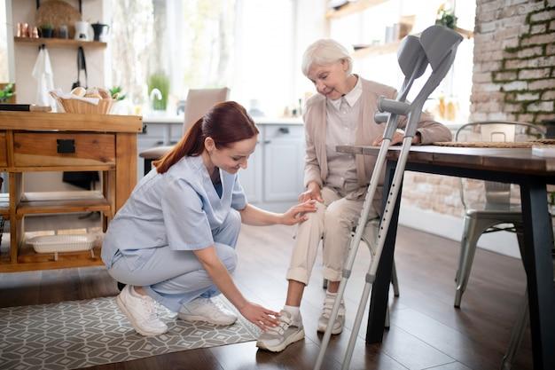 Infermiera che indossa l'uniforme prendersi cura della donna anziana