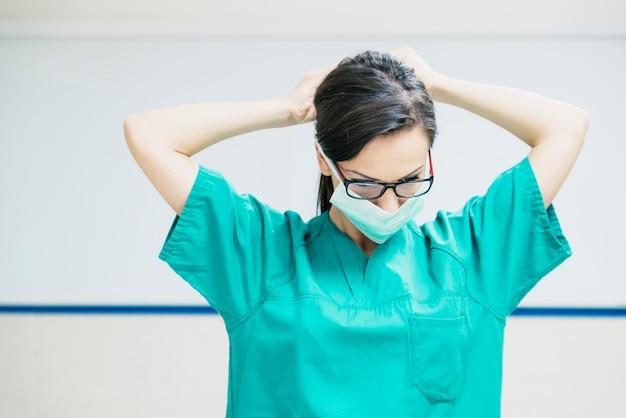 Infermiera che lavora mettendo la sua maschera medica
