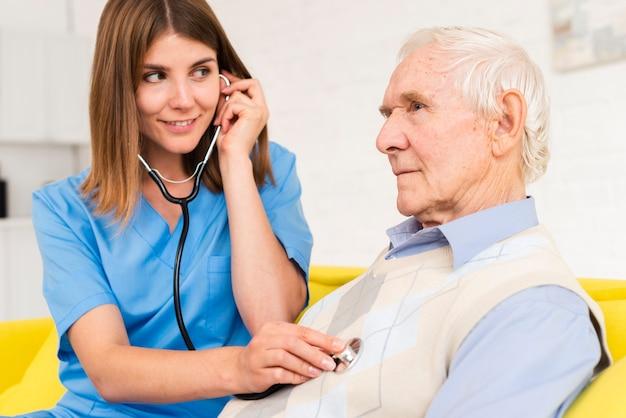 Infermiera che per mezzo dello stetoscopio sull'uomo anziano
